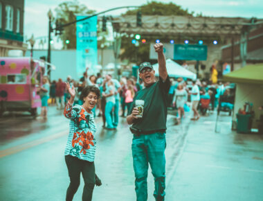 man and woman holding up drinks in street during festival