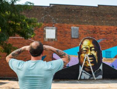 man looking at mural on brick wall